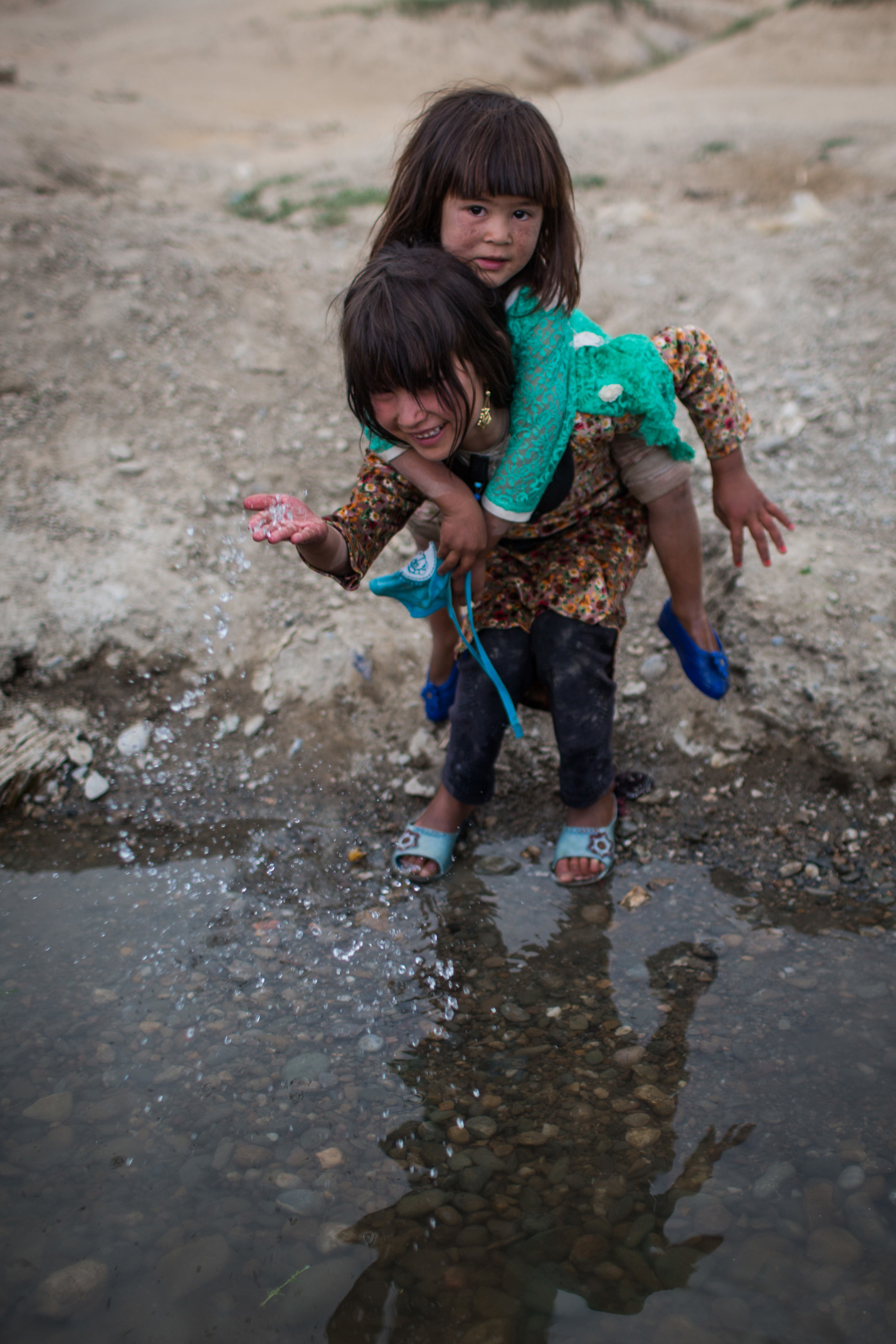 A little girl is pictured standing with her toes dipped in a puddle of water with pebbles at the bottom. She is laughing as she splashes some water with her hand. Another girl is on the first girls back with her arms wrapped around her neck.